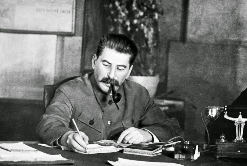 Сталин за столом с трубкой height=403
