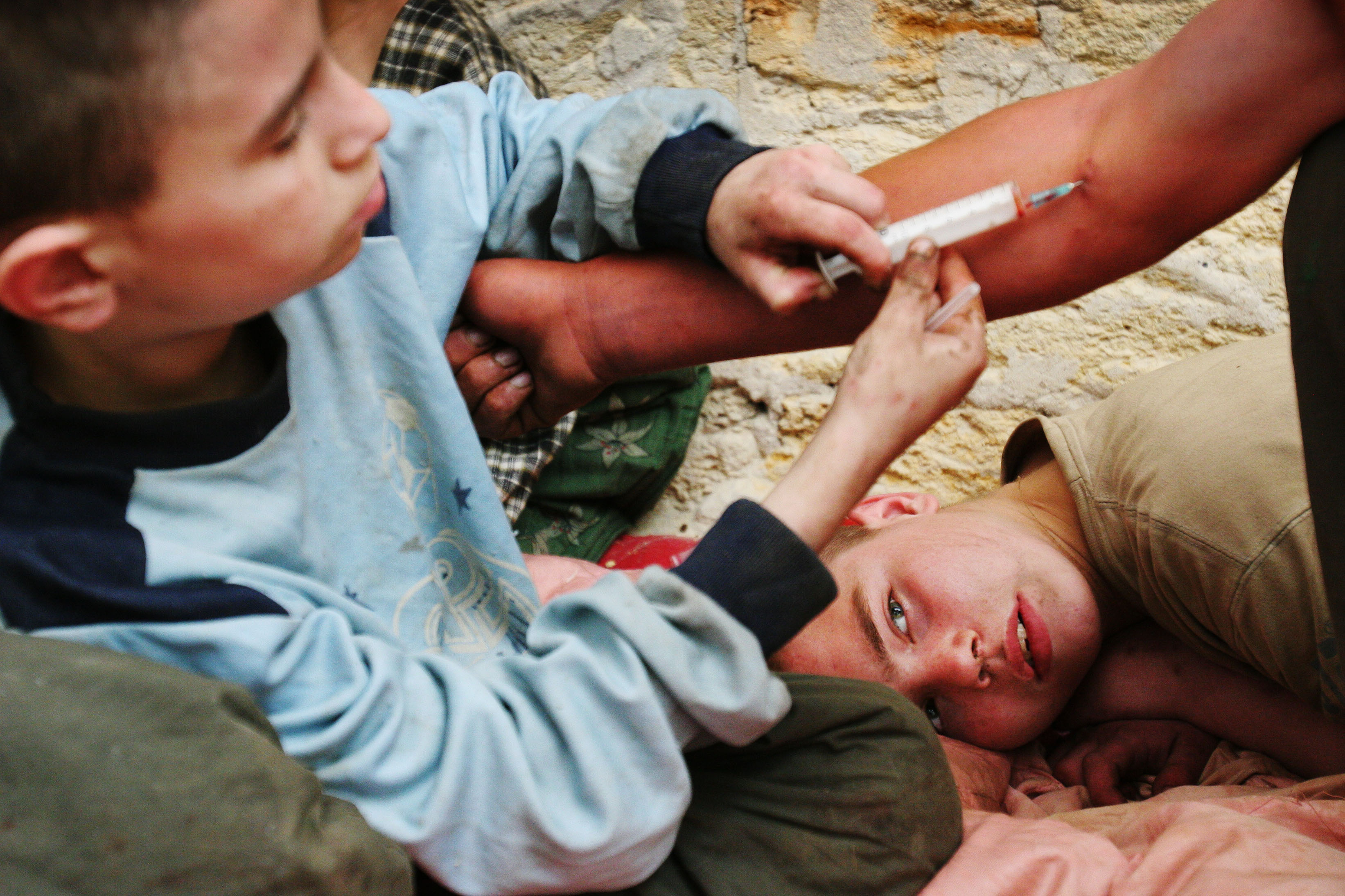 """June 17, 2006 - Denis """"Moldavanchik"""", 12 injects self made drug based on ephedrine known as """"baltushka"""" to his friend while Konstantin Golubenko, 17 looks at it in abandoned house where they live in Odessa, Ukraine on Saturday, June 17, 2006. According to Ukrainian NGO """"The Way Home"""" there are more then 3000 homeless children living in the street of Odessa. Almost all street children use drugs. The last research carried out by """"The Way Home"""" shows that practically all street children have STDs and many of them are HIV positive."""