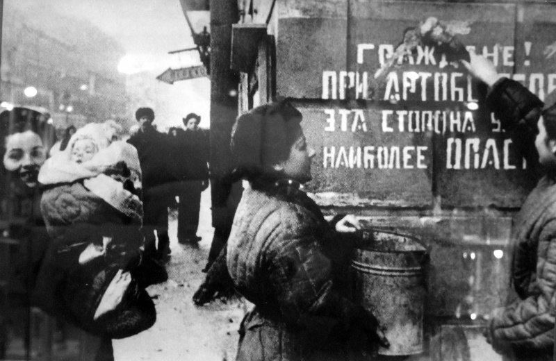 Ленинградцы закрашивают надпись на стене дома, предупреждающую об артобстрелах, после окончательного освобождения города от вражеской блокады.