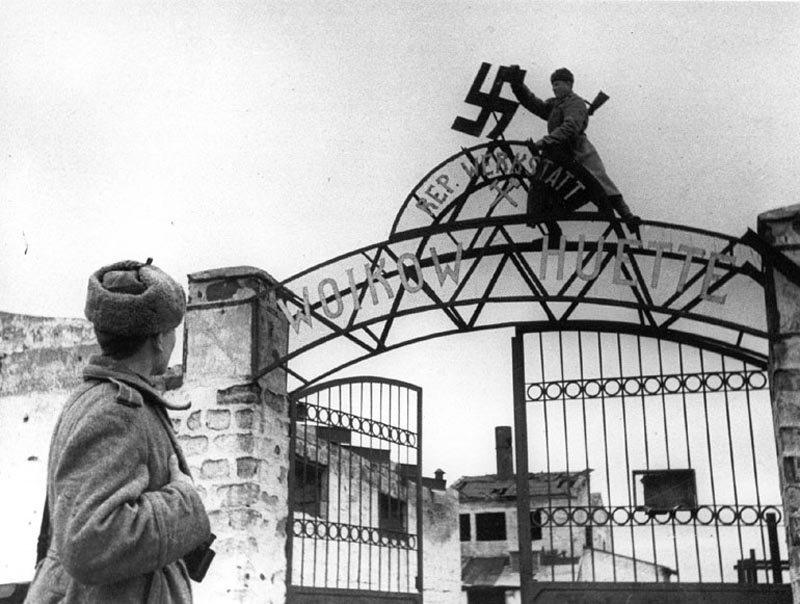 Освобождение Керчи. Советский солдат сбрасывает нацистскую свастику с ворот металлургического завода им. Войкова