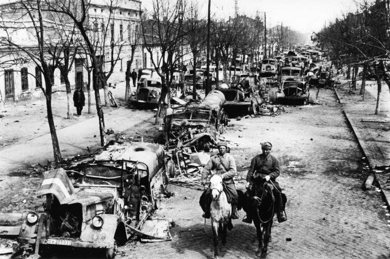 Советские солдаты едут по улице освобожденной Одессы. Улица забита техникой, брошенной немцами