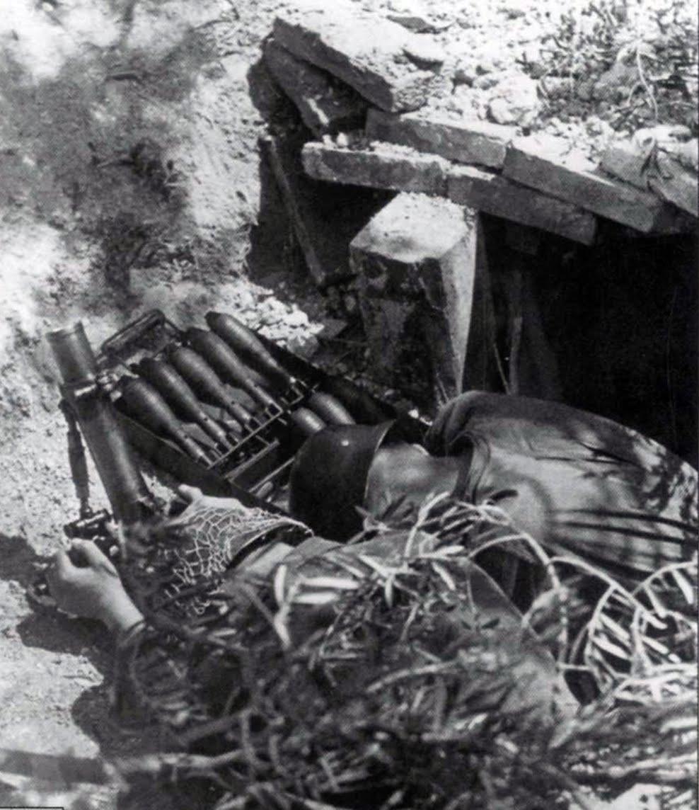 Немецкие солдаты ведут огонь из 50-мм миномета из укрытия в Монте-Кассино