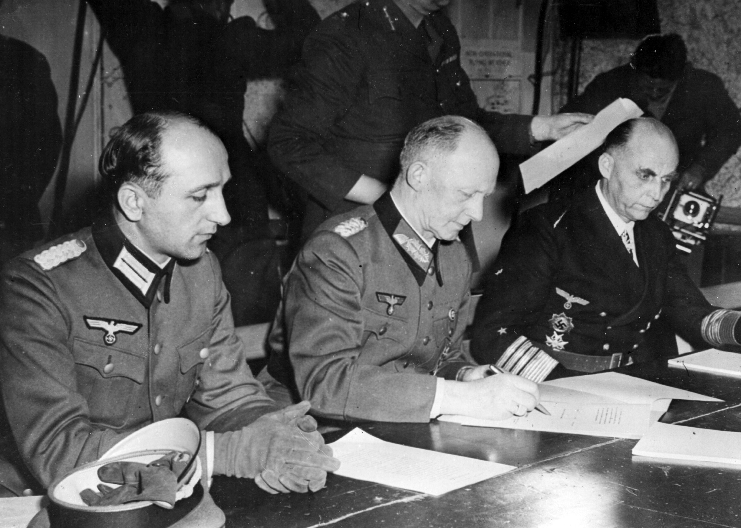 7th May 1945: German soldier and Chief of the Operations Staff Alfred Jodl (1890 - 1946) flanked by his aide on the left and Grand Admiral Hans Georg von Friedeburg on the right, signs the unconditional surrender document imposed by the Allies at General Eisenhower's HQ in Reims. (Photo by Hulton Archive/Getty Images)