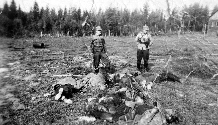 Финские солдат и офицер у тел расстрелянных на окраине Петрозаводска советских пленных. Время съёмки 1942г