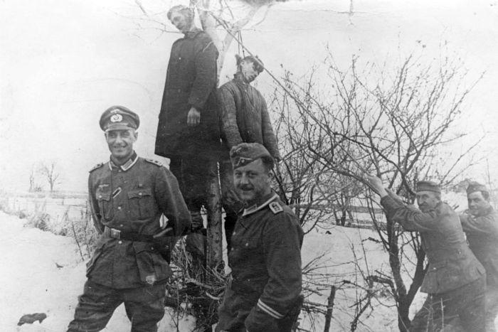 Немецкие солдаты фотографируются на фоне двоих повешенных советских партизан. Дополнительной информации о фото нет.