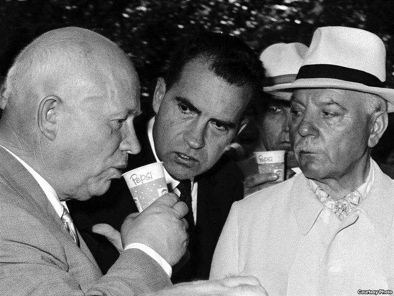 Никита Хрущев (слева) пьет пепси-колу, за ним наблюдает Ричард Никсон (в центре). Американская выставка в Москве, июль 1959 года