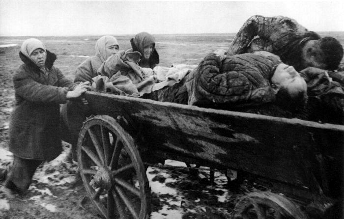 Советские женщины толкают телегу с телами расстрелянных немцами мужчин. 1942г.