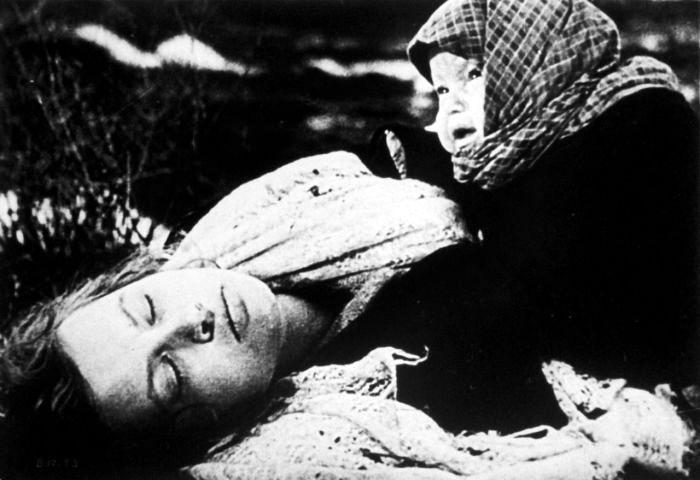 Советский ребенок, плачущий над телом своей погибшей матери. Кадр из советского фильма времен войны. 1942г