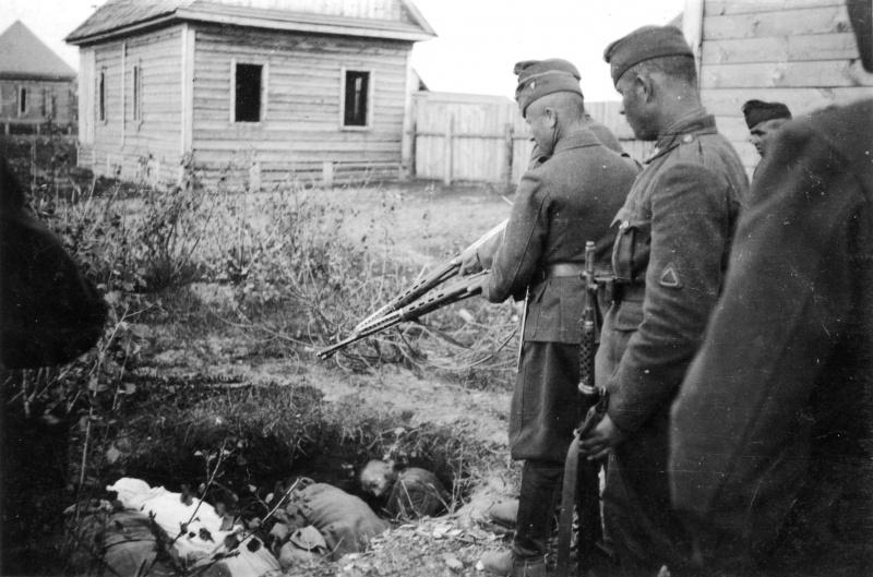 Венгерские солдаты с трофейными советскими винтовками СВТ-40 у ямы с расстрелянными советскими мирными жителями.
