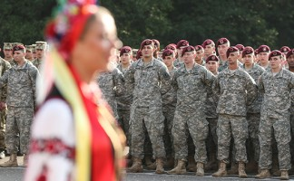 """YAVOROV, UKRAINE - SEPTEMBER 15:  Members of the U.S. Army 173rd Airborne Brigade stand at attention as a Ukrainian folk dance group performs at the opening ceremony of the """"Rapid Trident"""" NATO military exercises on September 15, 2014 near Yavorov, Ukraine. The two-week exercises include participating units from a variety of NATO and NATO-associate countries as well as Ukrainian troops. Meanwhile fighting between pro-Russian separatists and Ukrainian armed foces has flared again in eastern Ukraine in a battle for the control of Donetsk airport  despite the tenuous ceasefire.   (Photo by Sean Gallup/Getty Images)"""