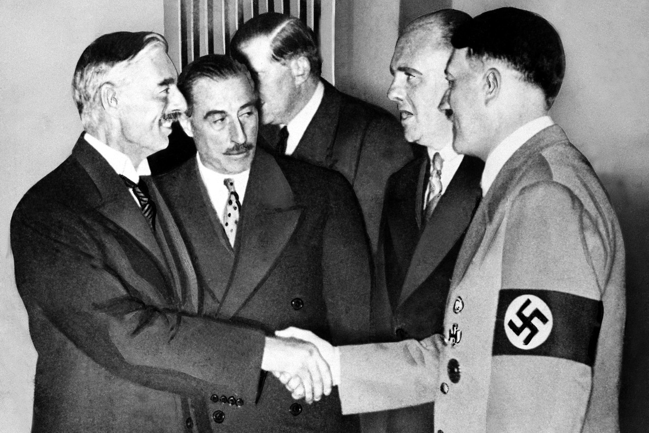 Hands clasped in friendship, Adolf Hitler and England's Prime Minister Neville Chamberlain, are shown in this historic pose at Munich on Sept. 30, 1938. This was the day when the premier of France and England signed the Munich agreement, sealing the fate of Czechoslovakia. Next to Chamberlain is Sir Neville Henderson, British Ambassador to Germany. Paul Schmidt, an interpreter, stands next to Hitler. (AP Photo)